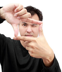 man_looking_through_fingers_in_shape_of_a_frame