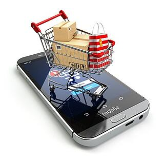 mini shopping cart sitting on top of mobile phone