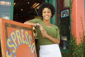 small_business_owner_standing_outside_shop-woman_in_apron