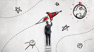 man drawing rocket to reach goals