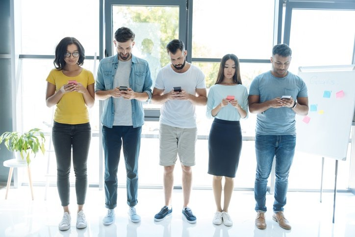 Millennials standing with their phones