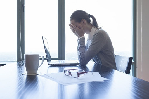 woman crying into her hands while at her desk