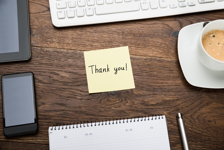 thank you written on a post it note on top of a desk