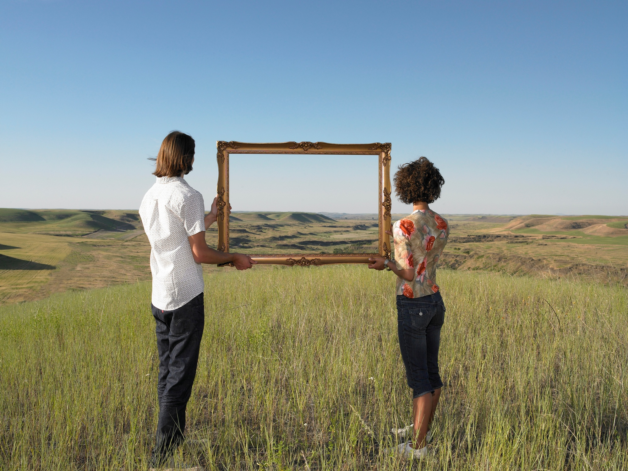 two people in a field holding a picture frame